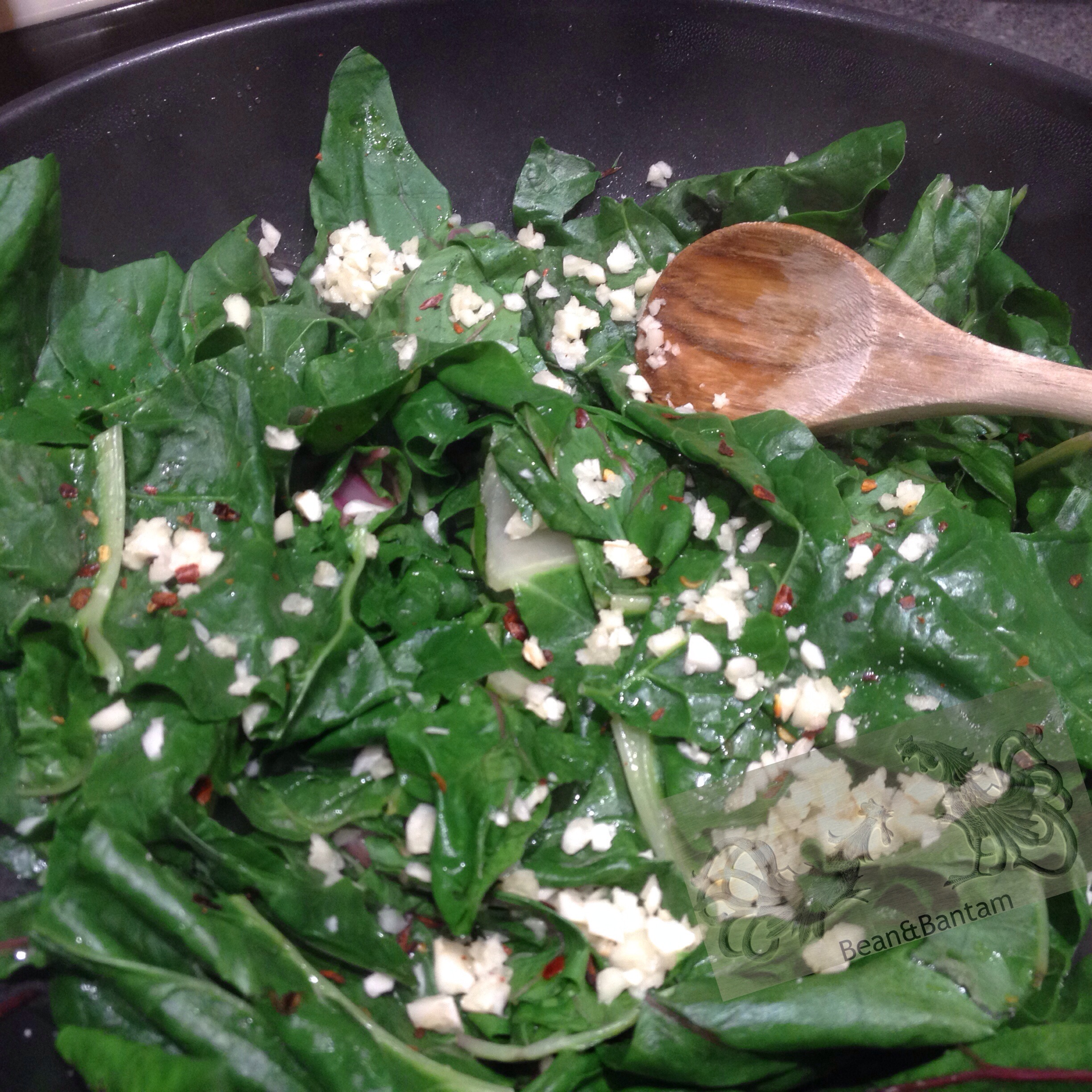 Adding in the garlic and the red pepper flakes. to the wilted chard