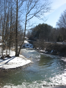 The river is high, the banks still snowy, a Sunday walk in Vermont